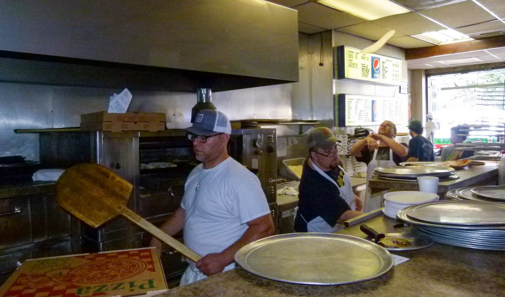 Ben Sciulli works the ovens while Michael Scheirer stretches pizza dough by tossing it in the air at Milano's. Shawn Stockdale works on an order between the two.