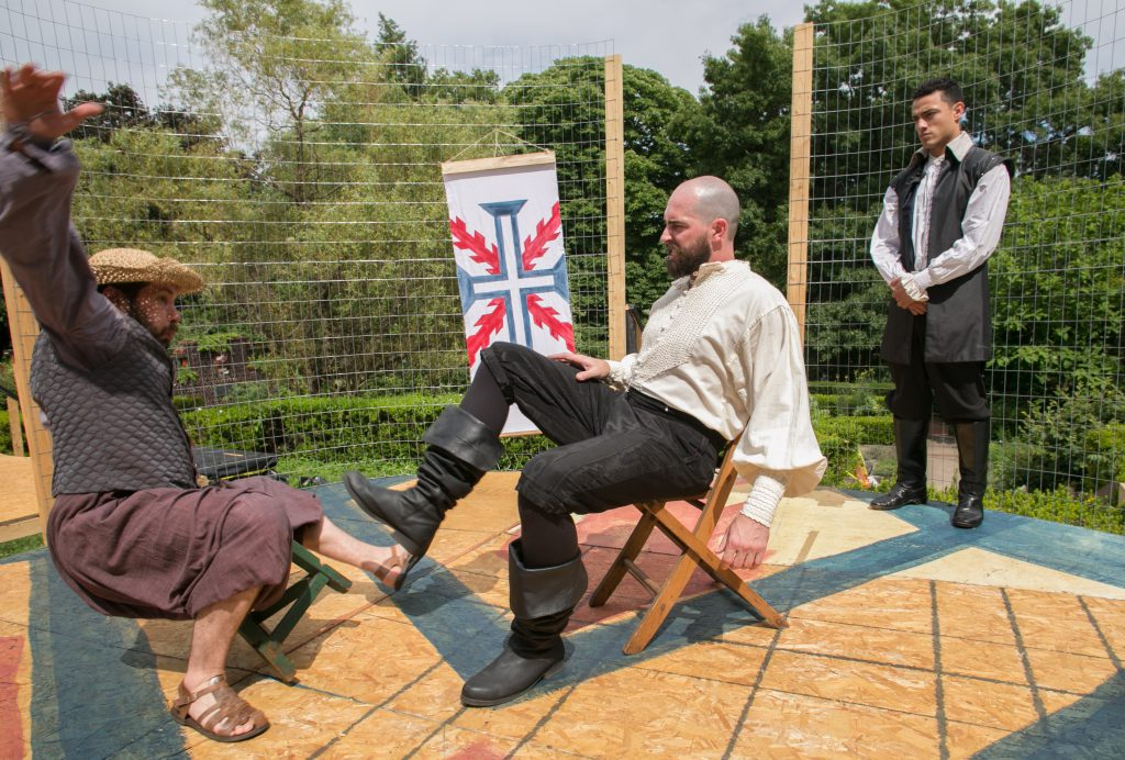 The Commander (Mike Mihm) pushes his man servant Lujan (Don DiGiulio) with his foot as Leonardo (Freddy Miyares) looks on.