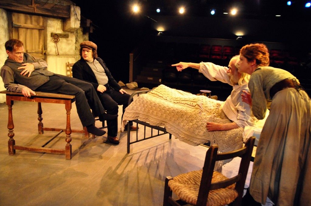 Dinzie is startled as Donal rises up on his death bed to angrily point at him. Jack looks on and Trassie (Karen Baum) tries to comfort her father.