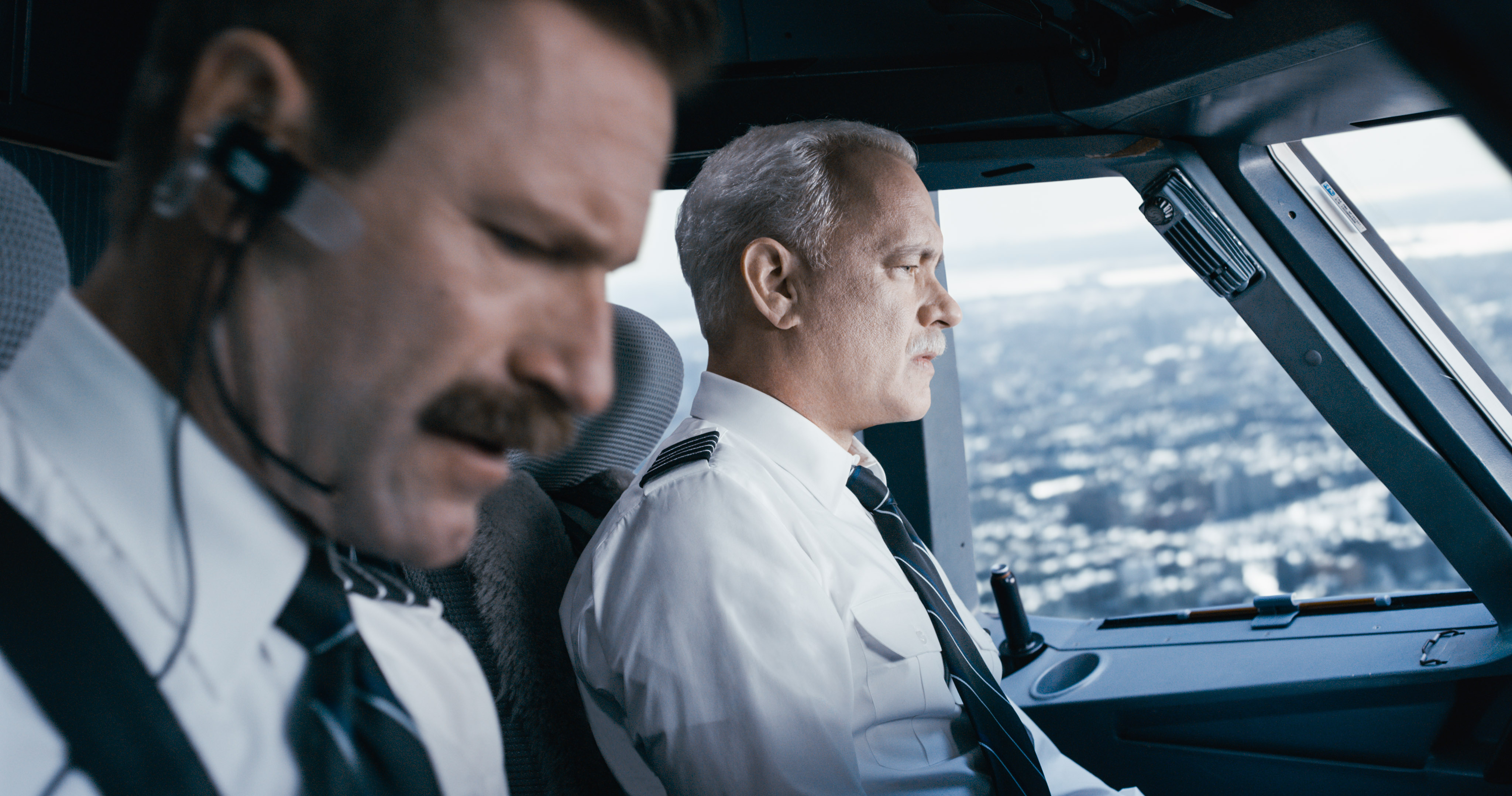"""Captain """"Sully"""" Sullenberger (Tom Hanks) keeps a steady eye on the situation while first officer Jeff Skiles (Aaron Eckhart) checks the emergency handbook."""