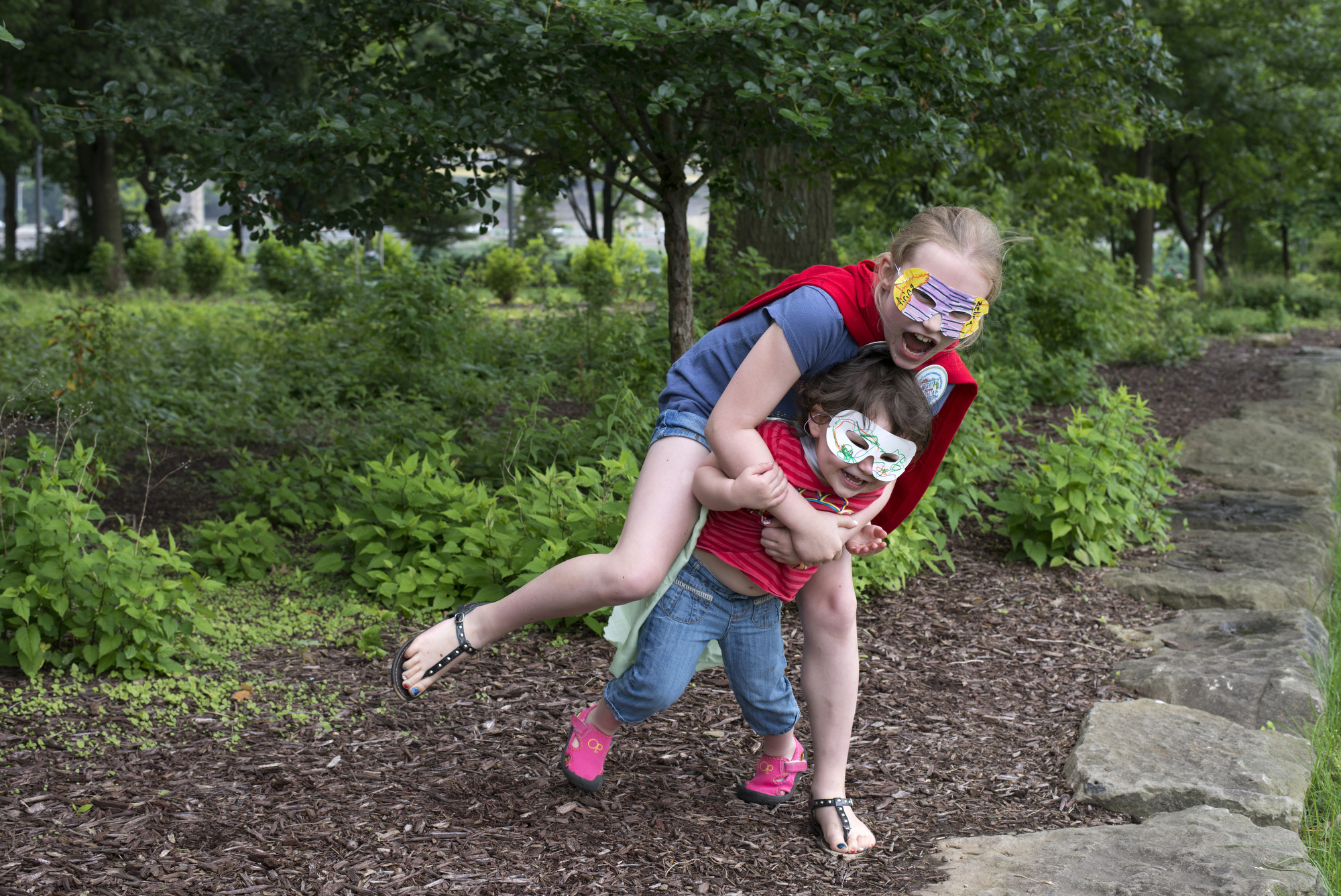 Superheroes Amanda Palmer, 9, and younger sister Jayda , 2, of Economy play at Point State Park after making masks and capes at Giant Eagle's Creativity Zone.