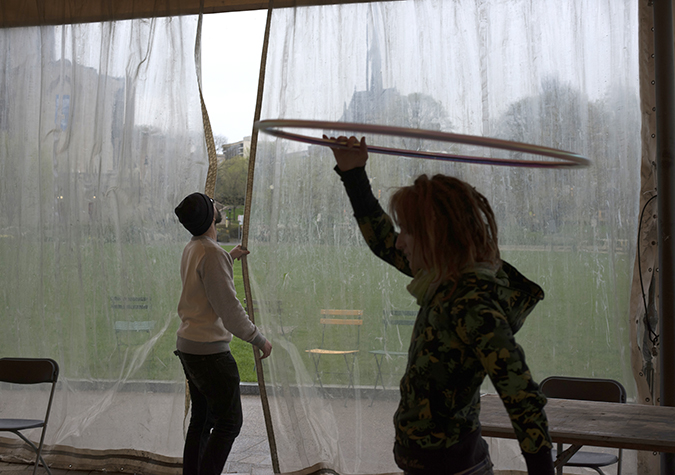Alex Sadlo, of the Pittsburgh Flow Collective, dances while volunteers adjust a rain curtain at the Schenley Plaza pavilion.