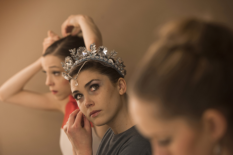 Corps dancer Caitlin Peabody puts on earrings as she prepares for her role as Snow Queen backstage with other leading ladies.
