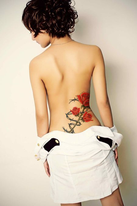 Beautiful red rose branch tattoo on lower back