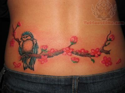 Owl on branch of flowers tattoo on lower back