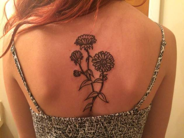 black and white aster flower tattoo on back