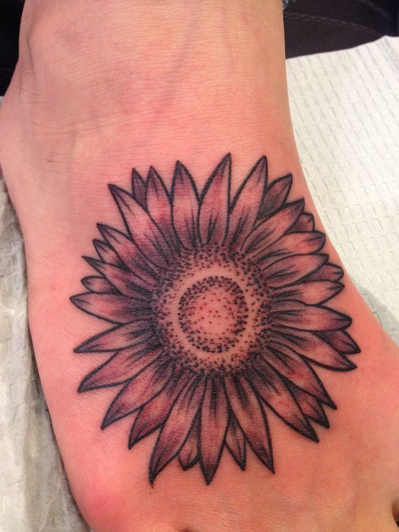 black and white aster flower tattoo on foot