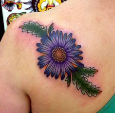 blue aster flower tattoo with green leaves