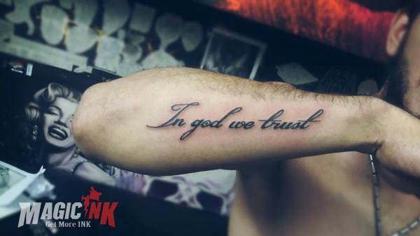 amazing text in god we trust tattoo on forearm