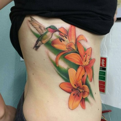 tiger lily flowers tattoo with colorful hummingbird on side