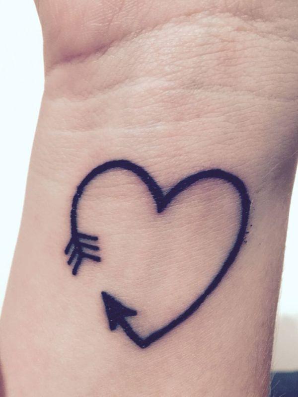 arrow heart outlined tattoo on wrist