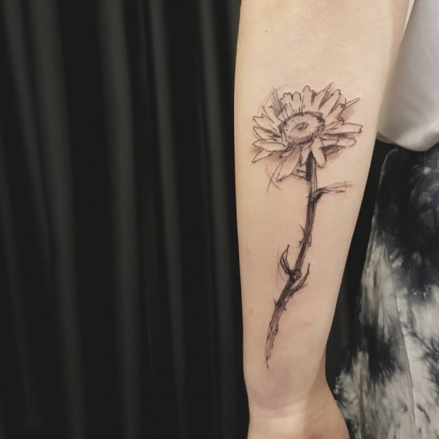 daisy flower drawing tattoo on side forearm