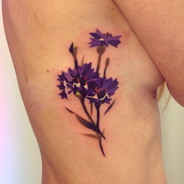 abstract cornflowers tattoo design on rib cage for women