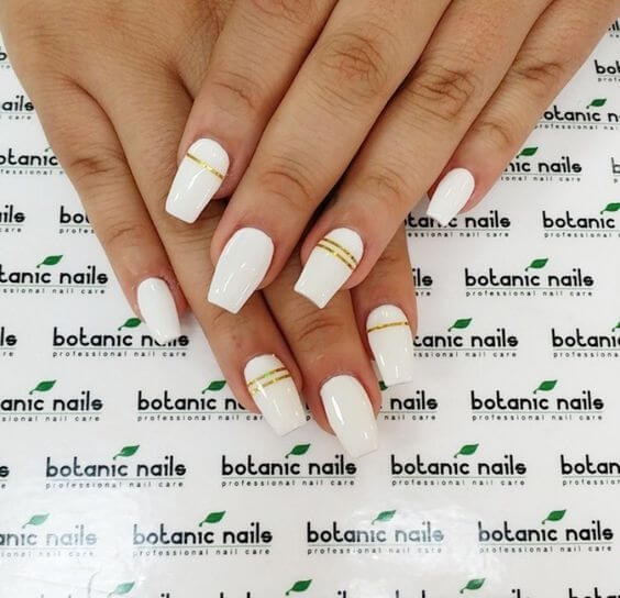white coffin nails with golden stripe lines