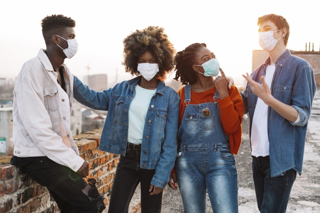 Group of young friends hanging out with medical masks