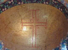 The Greek cross and inscription embedded in gold mosaic are typical of Byzantine church decoration