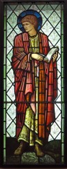 Stained glass window showing St Paul standing holding an open book, looking off to one side