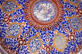 Red, blue, and gold intricate patterns on a white ground cover the inside of a dome in the Blue Mosque