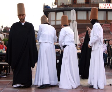 Four dervishes remove their cloaks before they begin their whirling ceremony