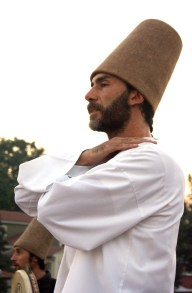A dervish with a tall hat about to start dancing, arms clasped at his chest