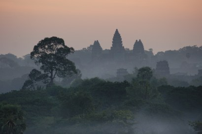 The towers of Angkor Wat seen from a distance appearing out of morning mist