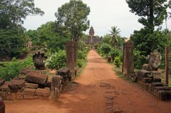 View of Bakong temple from a distance, looking down a dirt causeway towards the centre of the temple.