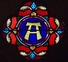 One of two tiny roundels over the altar of All Saints' church, this is the sign for 'alpha', as in 'I am the alpha and the omega', i.e. the beginning and the end.