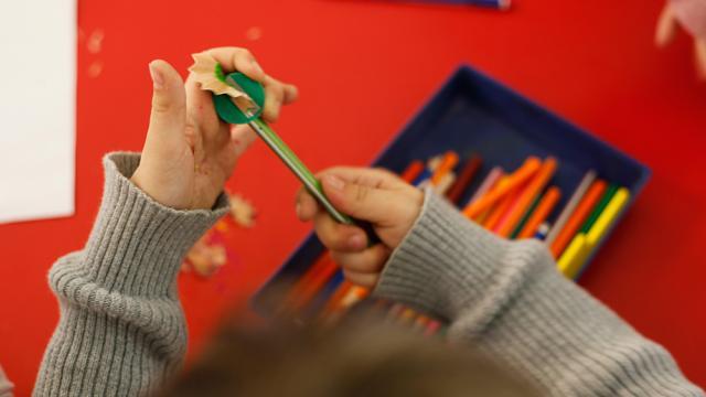 Un niño saca punta a su lápiz en una escuela española. / Unicef
