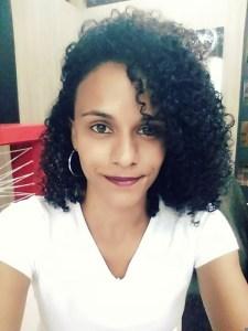 Priscila é negra, tem cabelos cacheados pretos na altura dos ombros. Tem olhos castanhos, usa brincos de argola, batom escuro e sorri. Veste blusa branca.