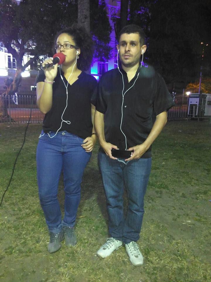 Bruna e Leonard de pé. Ambos vestem camisa preta, calça jeans e usam fones de ouvido brancos. Bruna está à esquerda e segura um microfone. É noite. Estão no meio da praça da República.