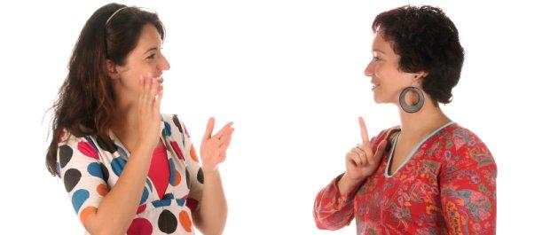 Duas mulheres de pele clara frente a frente. Sorriem e gesticulam.