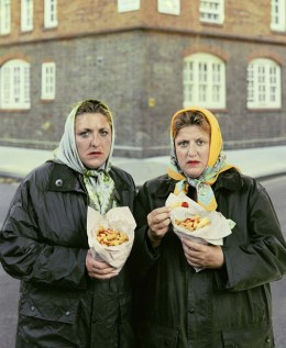 Sisters in scarfs eating Pimlico chips. David Stewart