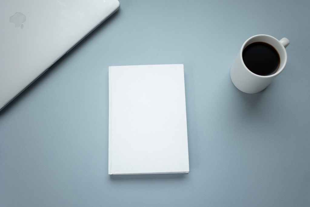 cup of coffee and laptop near empty notebook on table