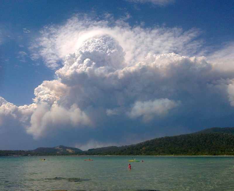 A layer of smoke underlies a towering cumulonimbus cloud above a beach in Australia.