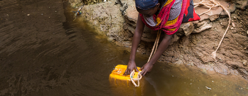 a woman fills a container with water from a river