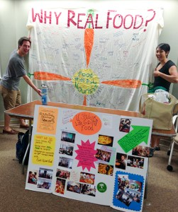 two students pose by the why real food banner