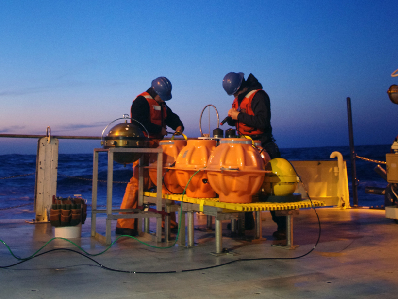 Engineers decommissioning an ocean bottom seismometer and differential pressure gauge