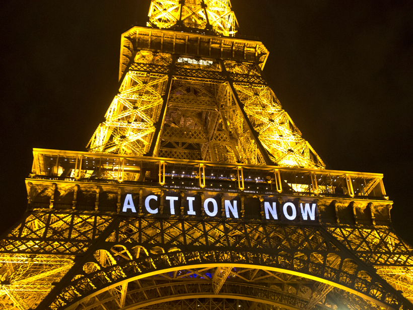 """The Eiffel Tower in Paris lights up with the slogan """"Action Now."""""""