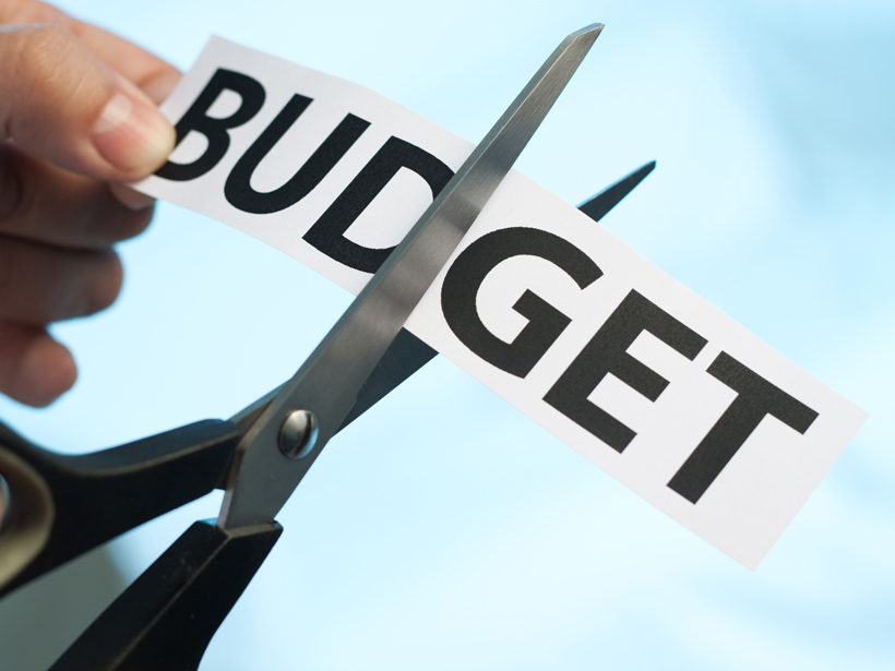 "Scissors cutting the word ""budget."""