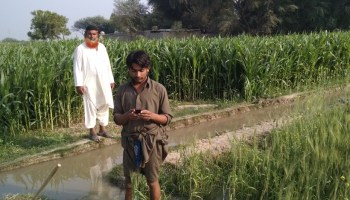 A Pakistani farmer checks his cell phone for weather updates and irrigation water estimates.
