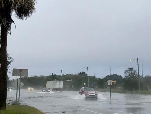 Cars splash through a flooded East Bay Street in Charleston, S.C.