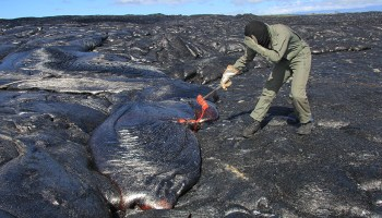 A scientist at Kīlauea gathers molten lava samples for research and monitoring of lava composition and chemicals.