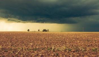 Storm clouds gather over dry farmland in Nebraska.