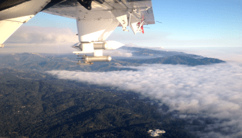 A Twin Otter turboprop flies over California, taking measurements of smoke from a wildfire.