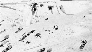 Trucks assemble outside an icy entrance to Camp Century in Greenland.