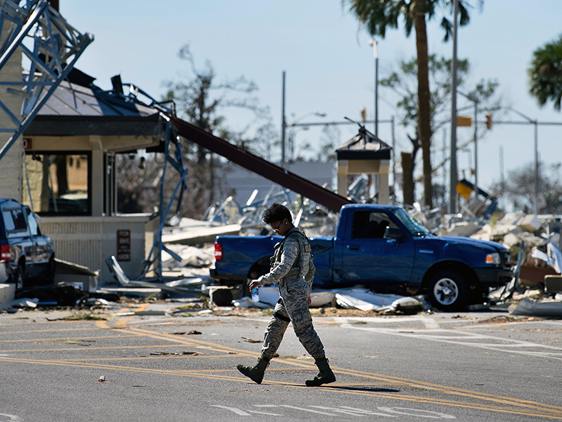A military police officer walks by a gate destroyed by Hurricane Michael at Tyndall Air Force Base in Florida.