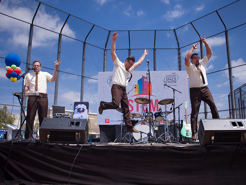 Three white guys in shirtsleeves perform on an outdoor stage.