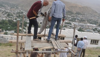 Men working on a makeshift platform in front of a populated valley