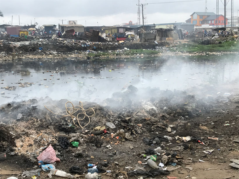 Steam rises from garbage and a polluted river.