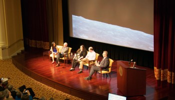 Panelists sit on a stage in front of a photo of the Apollo Moon landing.
